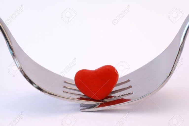 16693484 Simboleggia cena romantica per due con due forchette e un cuore rosso su sfondo bianco Archivio Fotografico